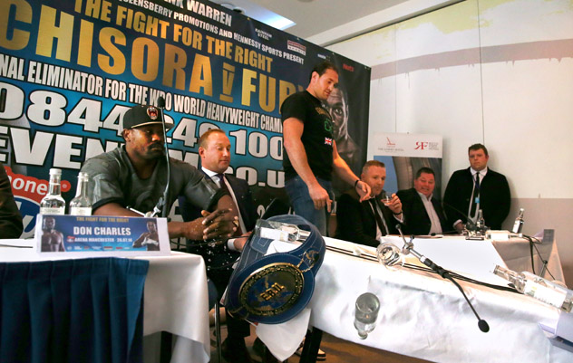 Tyson Fury (standing) knocks over a press conference table as July 26 opponent Dereck Chisora looks on. Photo by Alex Livesey/Getty Images.