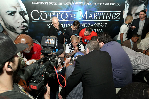 Miguel Cotto (center) speaks to reporters at an April 10, 2014, press event to announce the signing of Wilfredo Vazquez to Cotto Promotions. Photo by Chris Farina/Top Rank.