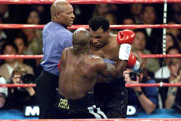 Referee Richard Steele forces his way between Mike Tyson (R) and Orlin Norris on Oct. 24, 1999. Photo by Hector Mata/APF-Getty Images.