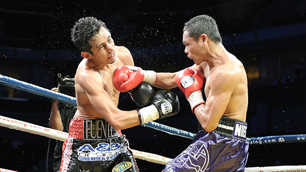 Donnie Nietes (R) connects with Moises Fuentes on the way to winning THE RING jr. flyweight title on May 10, 2014. Photo by Denmark Delores.