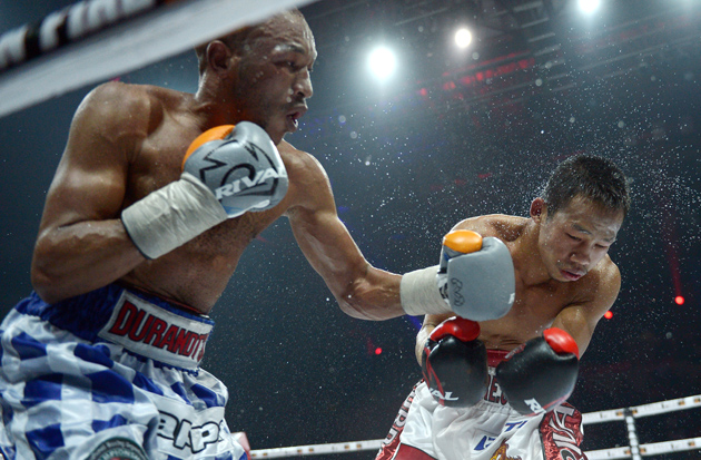 South African challenger Simpiwe Vetyeka (left) cracks Daud Yordan with a left en route to stopping the Indonesian standout in Round 12 of their featherweight title bout in Jakarta on April 14, 2013. Photo by Adek Berry/AFP/Getty Images