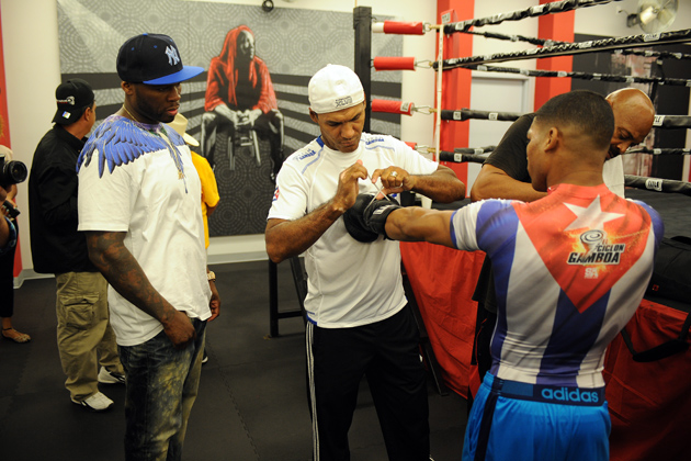 Curtis '50 Cent' Jackson (left) watches as his star fighter, Yuriorkis Gamboa, get his gloves tied for a media workout at Iron Mike Productions Gym on June 12 in Deerfield Beach, Fla. Photo by Larry Marano/Getty Images