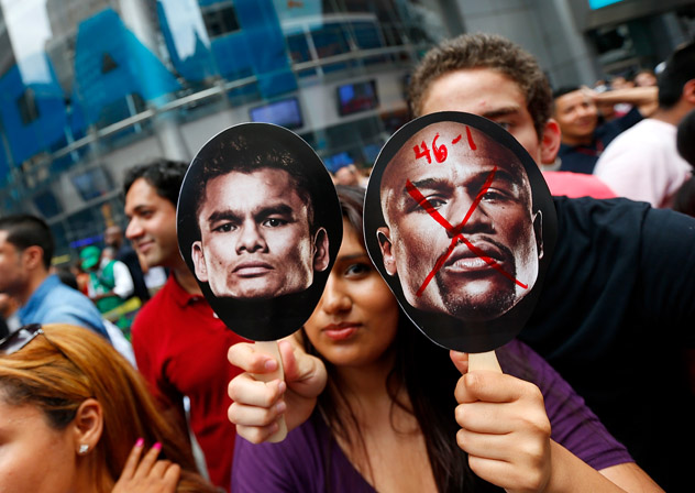 New York: A fan holds up signs outside the kickoff press conference for Floyd Mayweather Jr.-Marcos Maidana II. Photo by Mike Stobe/Getty Images.