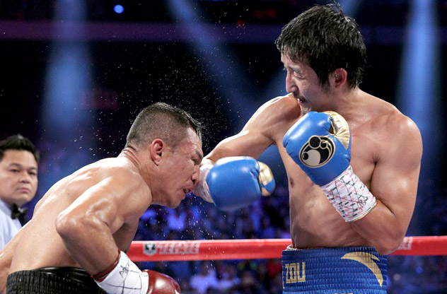 Zou Shiming (R) throws a right hook at Luis De La Rosa on July 19, 2014, in Macau. Photo by Chris Farina/Top Rank.