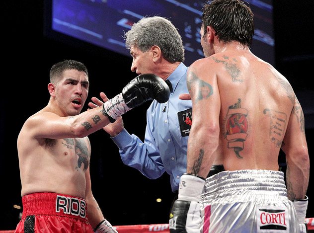 Brandon Rios (L) points the finger at Diego Chaves as referee Vic Drakulich steps in to give a warning. Photo by Chris Farina/Top Rank.