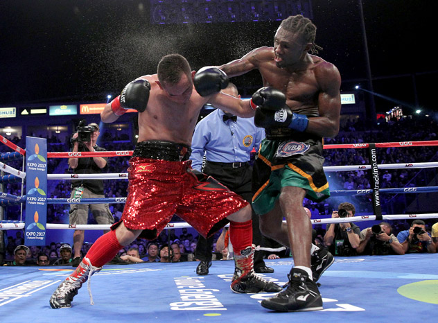 Nonito Donaire (L) absorbs a powerful right from Nicholas Walters in October 2014. Walters became the WBA featherweight champion with a sixth-round TKO. Photo by Chris Farina - Top Rank