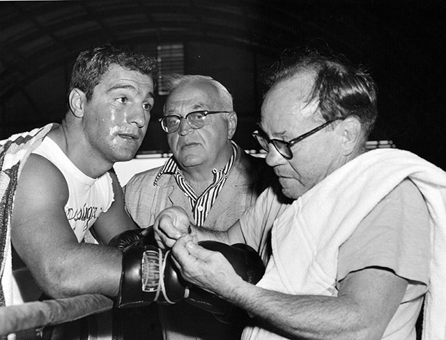 Rocky Marciano watches trainer Charley Goldman lace up his gloves as manager Al Weill looks on during a workout at Grossinger's Gym in New York prior to his heavyweight title defense against Archie Moore. Photo by THE RING magazine / Getty Images