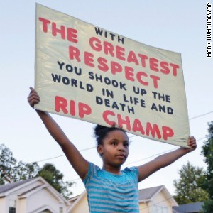Nine-year-old Akera Price-King holds up a sign in front of Muhammad Ali's boyhood home. Photo credit: Mark Humphrey/ Associated Press