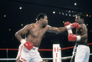 Holmes (L) attacks Michael Spinks in their rematch. Photo: THE RING