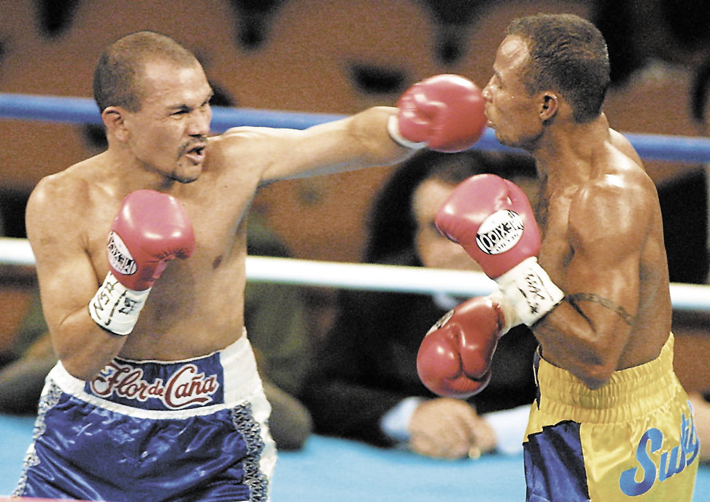 Rosendo Alvarez (left) connects with a left against WBA junior flyweight titlist Beibis Mendoza in March 2001 at the Mandalay Bay Resort and Casino in Las Vegas. Photo credit: Mike Nelson/La Prensa/AFP Photo