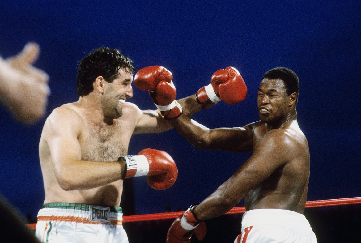 Larry Holmes (right) avoids Gerry Cooney's lethal left hook. Photo by The Ring Magazine
