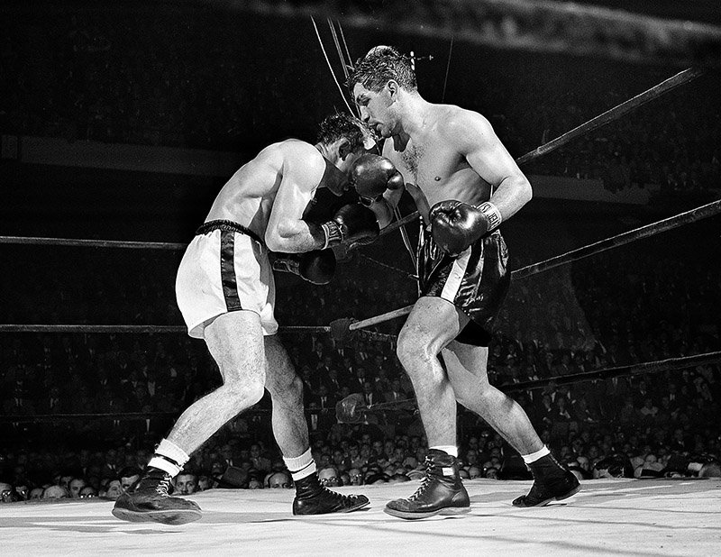 Tony DeMarco, right, lands a right to the head of Carmen Basilio in the seventh round of their rematch at the Boston Garden in November 30, 1955. (AP Photo)